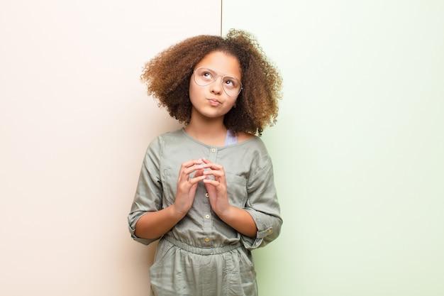 Afroamerikanisches kleines mädchen, das entwirft und verschwört, verschlagene tricks und betrüger denkt, gerissen und gegen flache wand verrät