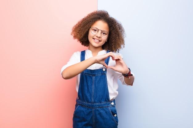 Afroamerikanisches kleines mädchen, das lächelt und sich glücklich, süß, romantisch und verliebt fühlt und herzform mit beiden händen gegen flache wand bildet
