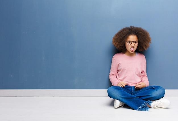 Afroamerikanisches kleines mädchen, das sich angewidert und gereizt fühlt, die zunge herausstreckt und etwas böses und glückliches nicht mag, das auf dem boden sitzt