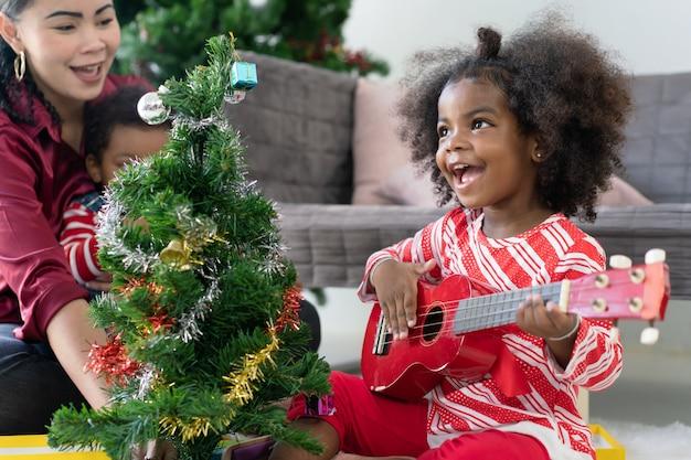 Afroamerikanisches kleines mädchen, das ukulelengitarre spielt, feierte weihnachten zu hause mit ihrer mutter