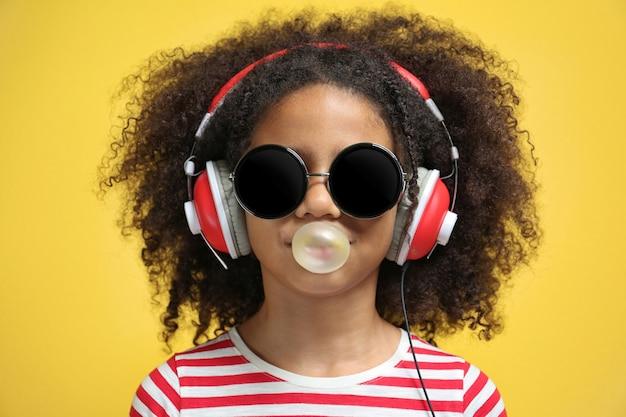 Afroamerikanisches kleines mädchen mit kopfhörern und sonnenbrille, die kaugummi auf gelb kauen