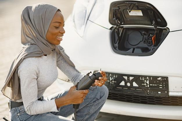 Afroamerikanisches mädchen, das elektroautos an der elektrotankstelle auflädt