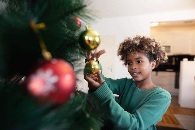 Afroamerikanisches mädchen, das weihnachtsbaum im gemütlichen innenraum verziert