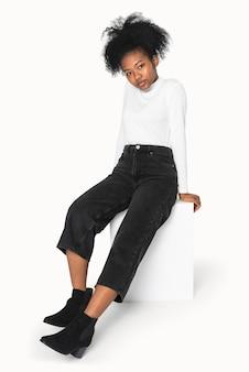 Afroamerikanisches mädchen in weißem rollkragenpullover und schwarzer jeans für winterbekleidungsshooting