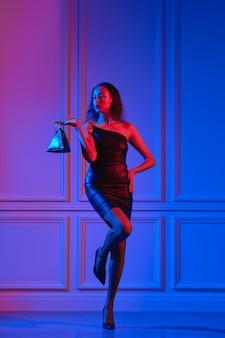 Afroamerikanisches modell im kleinen kleid, netzstrumpfhose hält dreieckige handtasche unter neonlicht