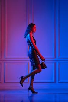 Afroamerikanisches modell in öko-lederkleid, netzstrumpfhose mit dreieckiger handtasche geht unter neonlicht