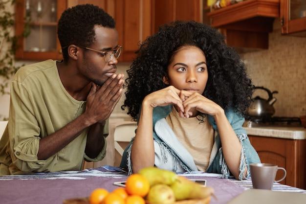Afroamerikanisches paar, das in seinen beziehungen schwere zeiten durchmacht. schuldiger untreuer junger mann, der die hände gedrückt hält und seine wütende frau bittet, ihm die untreue zu vergeben, und versucht, sie süß zu reden