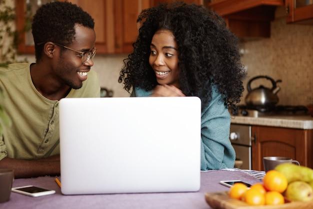 Afroamerikanisches paar, das laptop-computer zusammen zu hause verwendet. glückliche frau, die lächelt und ihren ehemann mit aufregung betrachtet, während sie flugtickets online kauft und plant, ferien am meer zu verbringen