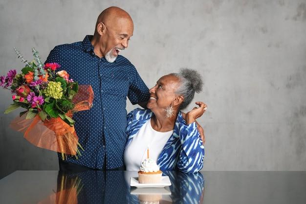 Afroamerikanisches paar feiert ein jubiläum zusammen mit blumen