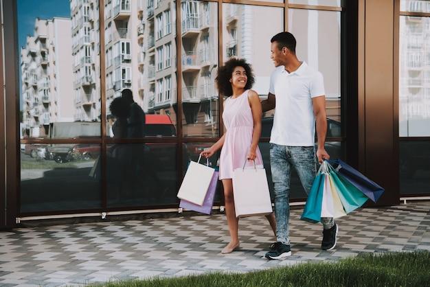 Afroamerikanisches paar geht mit einkaufstaschen spazieren