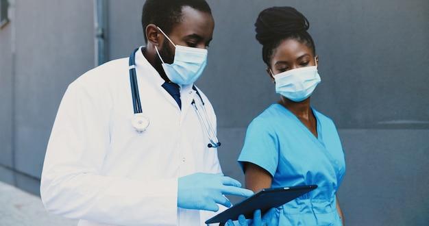Afroamerikanisches paar, mann und frau, ärztekollegen in medizinischen masken, die gehen, sprechen und tablet-gerät verwenden. männliche und weibliche ärzte tippen und scrollen auf dem gadget-computer. kommunikation