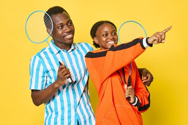 Afroamerikanisches paar mit schlägern, die auf etwas zeigen