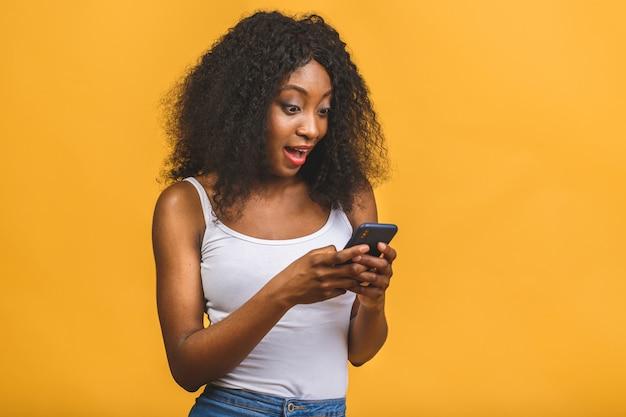 Afroamerikanisches schwarzes mädchen, das in den händen telefon hält, das auf dem web chattet