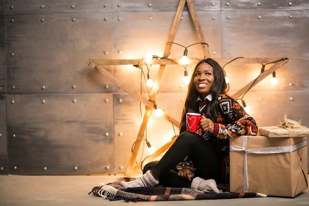 Afroe-amerikanisch frau, die kaffee an einem weihnachtsabend trinkt
