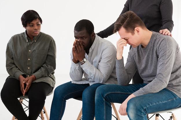 Afroe-amerikanisch frau, die traurige rehabilitationspatienten betrachtet