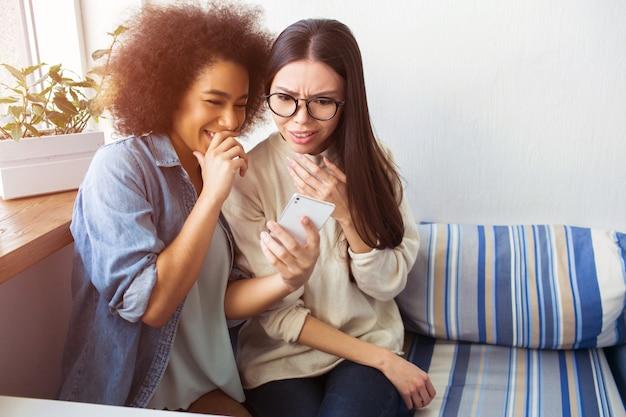 Afroe-amerikanisch mädchen hält ein telefon in ihren händen und huckling. sie zeigt ihrer freundin ein bild am telefon. mädchen im weißen pullover ist erstaunt. ihr gesicht zeigt viele emotionen.