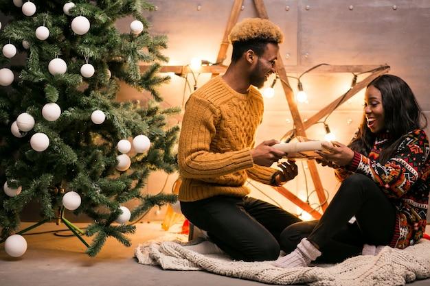 Afroe-amerikanisch paare, die durch den weihnachtsbaum sitzen