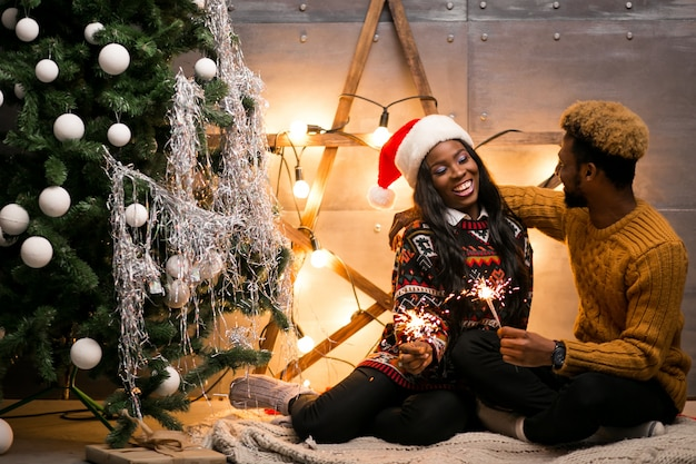Afroe-amerikanisch paare, die mit bengal-lichtern durch den weihnachtsbaum sitzen