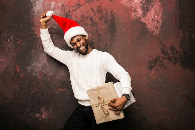 Afroer-amerikanisch mann, der weihnachtsgeschenke hält