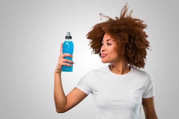 Afrofrau der jungen eignung, die ein energiegetränk trinkt