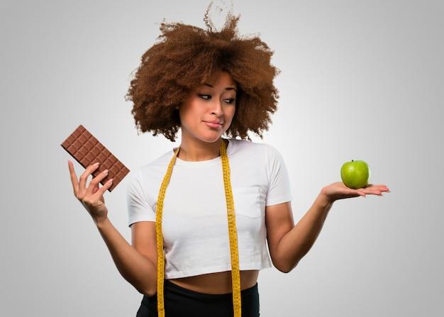 Afrofrau der jungen eignung, die zwischen dem essen gesund oder der schokolade wählt