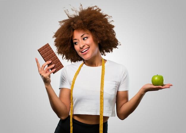 Afrofrau der jungen eignung, die zwischen dem essen gesund oder schokolade wählt