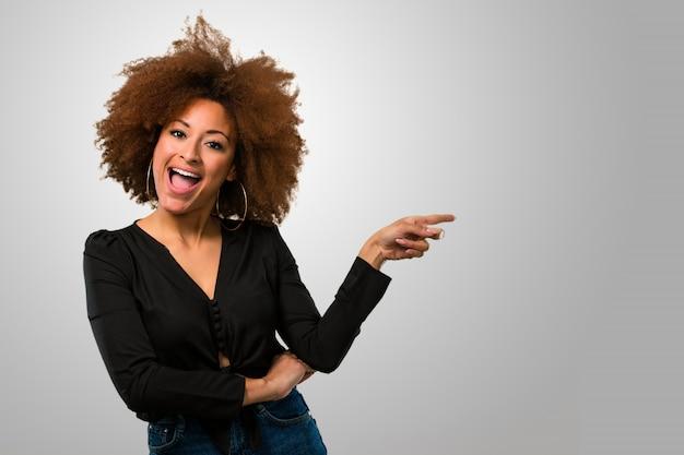 Afrofrau, die auf die seite zeigt