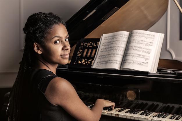 Afrofrau, die auf einem klavier spielt