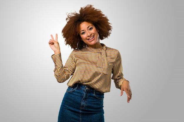 Afrofrau, die ein siegeszeichen tut