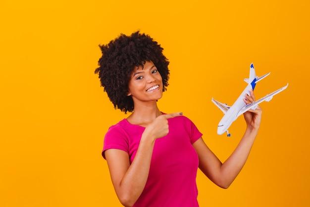 Afrofrau, die ein spielzeugflugzeug hält reisekonzept