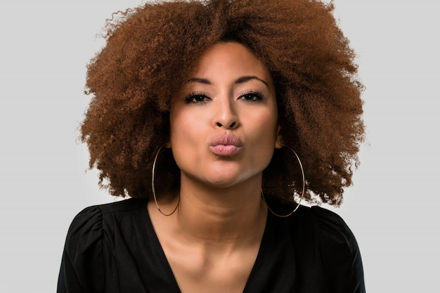 Afrofrau, die einen kuss, gesichtsnahaufnahme gibt