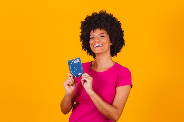 Afrofrauenlächeln, die brasilianischen pass in den händen halten