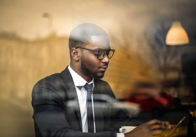 Afrogeschäftsmann, der seinen smartphone überprüft