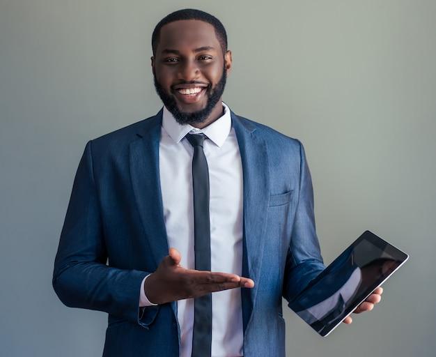 Afrogeschäftsmann zeigt eine digitale tablette
