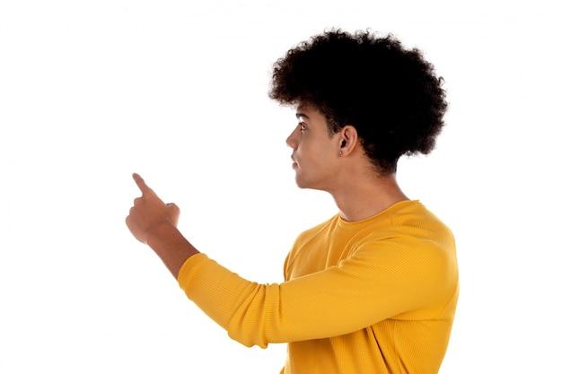 Afrojugendlicher mit gelbem t-shirt etwas mit seinem finger zeigend