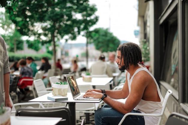 Afrokerl, der an einem laptop auf der terrasse eines cafés arbeitet