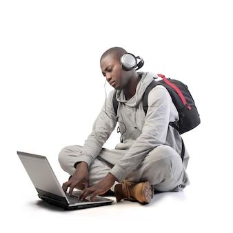 Afrokerl, der einen laptop verwendet