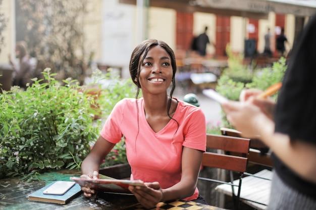 Afromädchen, das in einem bistro bestellt