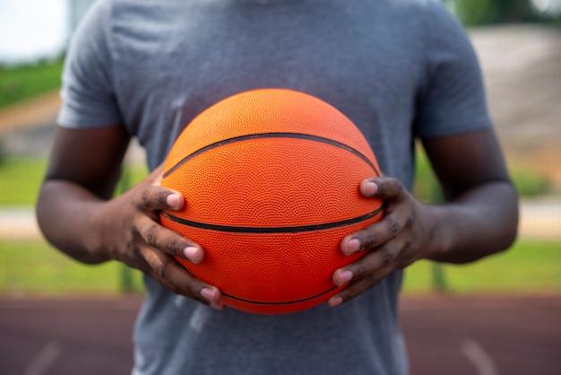 Afromann, der einen mittleren schuss des balls hält