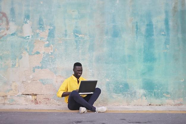 Afromann, der glücklich einen laptop verwendet
