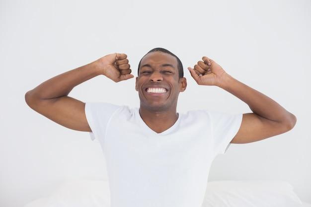 Afromann, der im bett aufwacht und seine arme ausdehnt