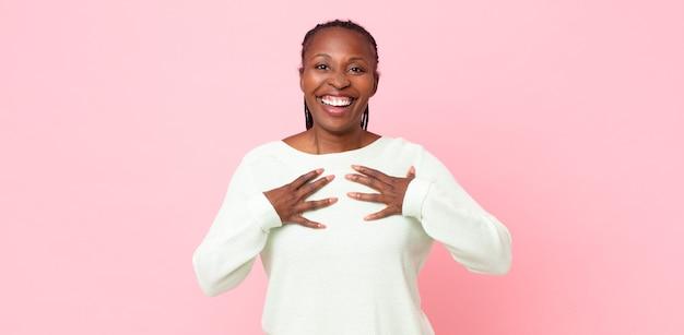 Afroschwarze erwachsene frau, die glücklich, überrascht, stolz und aufgeregt aussieht und auf sich selbst zeigt