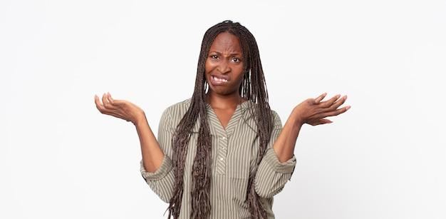 Afroschwarze erwachsene frau, die mit einem dummen, verrückten, verwirrten, verwirrten ausdruck die achseln zuckt und sich genervt und ahnungslos fühlt
