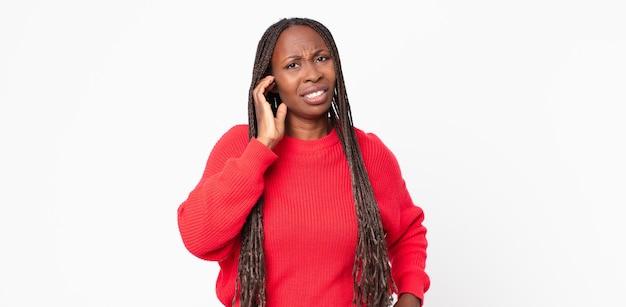 Afroschwarze erwachsene frau, die sich gestresst, frustriert und müde fühlt, schmerzenden nacken reibt, mit einem besorgten, unruhigen blick