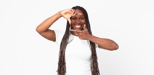 Afroschwarze erwachsene frau, die sich glücklich, freundlich und positiv fühlt, lächelt und ein porträt oder einen fotorahmen mit den händen macht