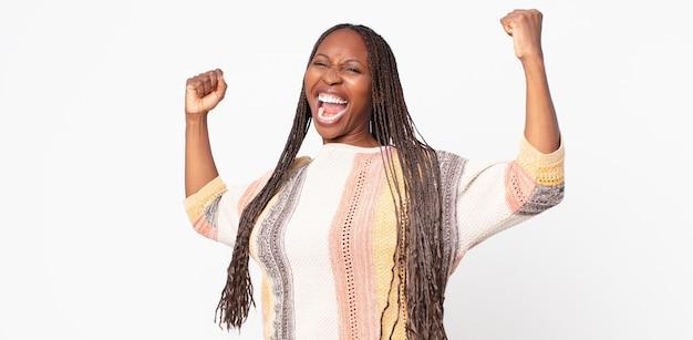 Afroschwarze erwachsene frau, die triumphierend schreit, wie aufgeregter, glücklicher und überraschter gewinner aussieht, feiert