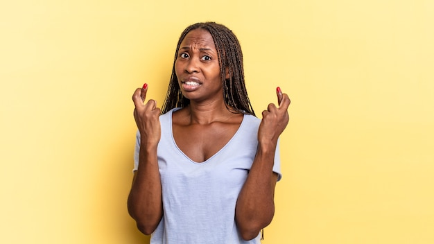 Afroschwarze hübsche frau, die ängstlich die daumen drückt und mit einem besorgten blick auf viel glück hofft