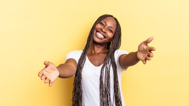 Afroschwarze hübsche frau, die fröhlich lächelt und eine warme, freundliche, liebevolle willkommensumarmung gibt und sich glücklich und bezaubernd fühlt