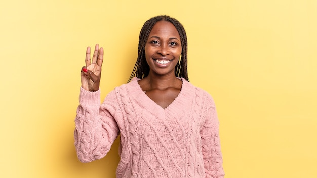 Afroschwarze hübsche frau, die lächelt und freundlich aussieht, die nummer drei oder die dritte mit der hand nach vorne zeigt und herunterzählt