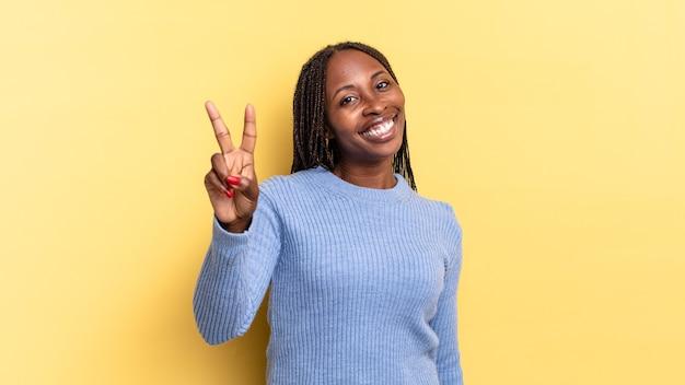 Afroschwarze hübsche frau, die lächelt und glücklich, sorglos und positiv aussieht und mit einer hand sieg oder frieden gestikuliert